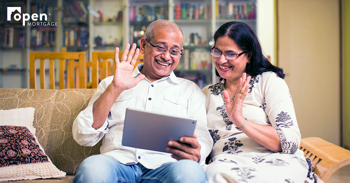 elderly couple waving at family through tablet